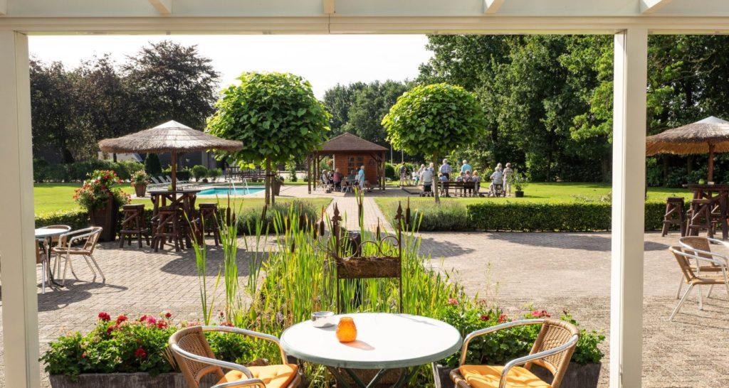 terras met vijver met tuion Zwembad seniorenhotel de Postelhoef